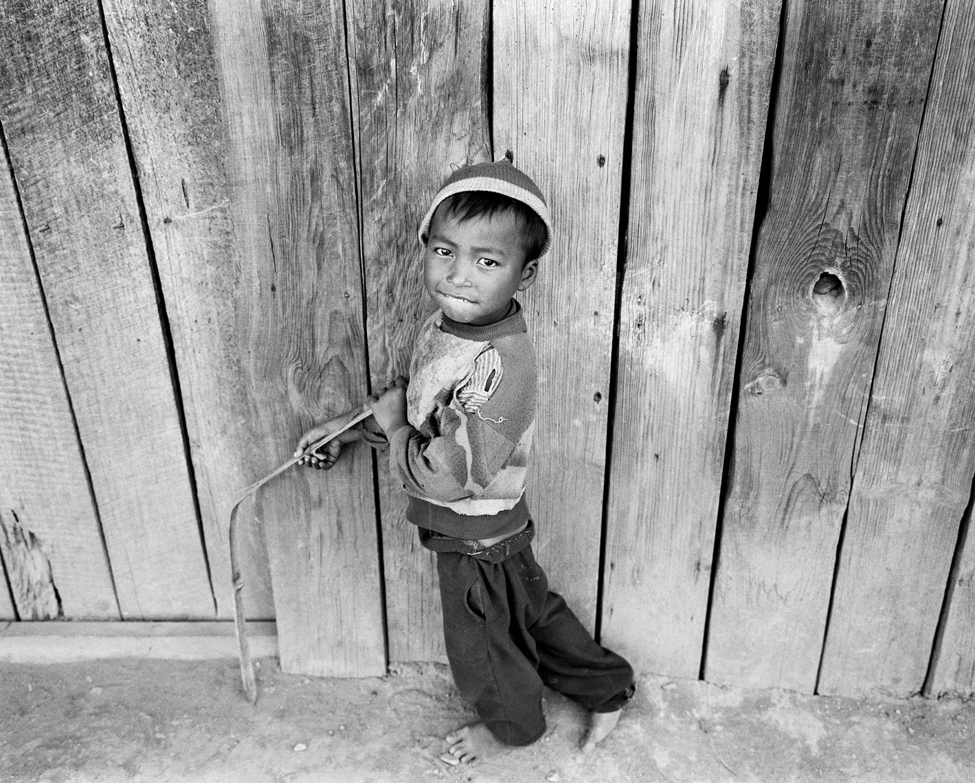 boy holding bamboo against house.jpg